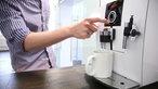 Mann zieht sich eine Tasse Kaffee am Kaffeeautomaten im Büro