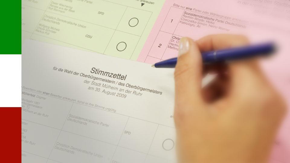 Eine Hand hält einen Stift über einen Stimmzettel.