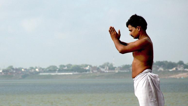 An Mann steht am Ganges und betet