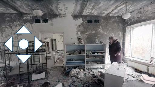 Navigationspfeile, Frau in zerstörtem Gebäude